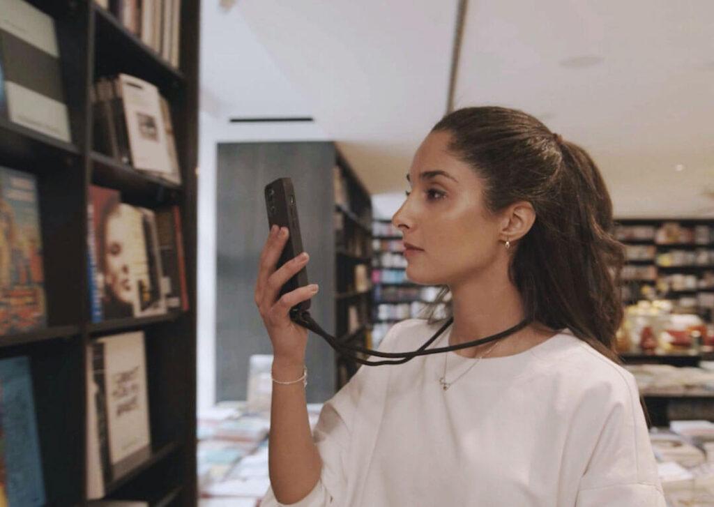 visually impaired women scanning books in a book store with dot go app